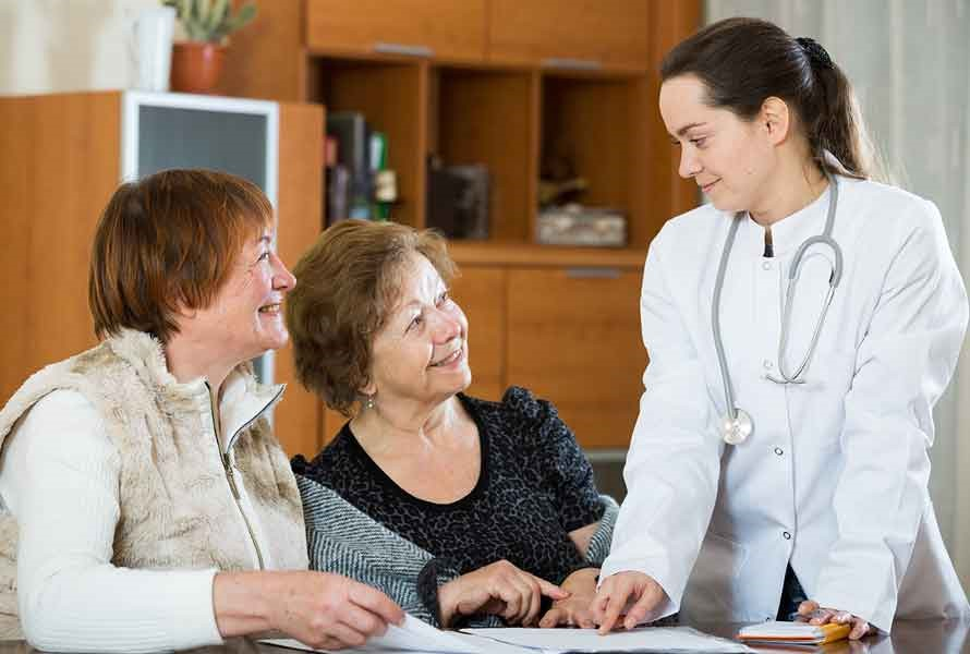 Stock photo of female doctor speaking with two older women